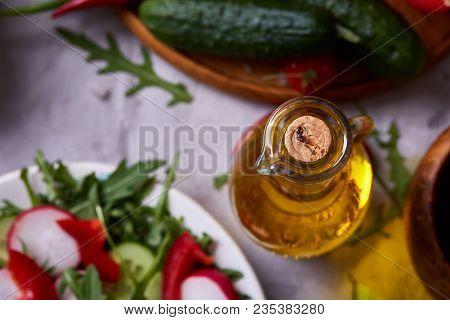 Tasty Still Life With Golden Olive Oil In Transparent Glass Jar Among Fresh Vegetables Over White Te