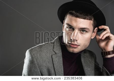 Portrait Of Concentrated Male Watching At Camera. He Isolated On Dark Background. Undistracted Styli