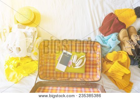 Suitcase With Winter And Summer Clothes On Bed. Preparing For Trip. Suitcase With Garment. Travel Co