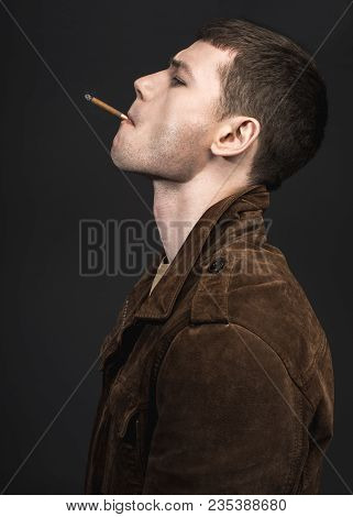 Side View Pensive Male Piping Cigarette. He Wearing In Modern Jacket. He Isolated On Black Backgroun