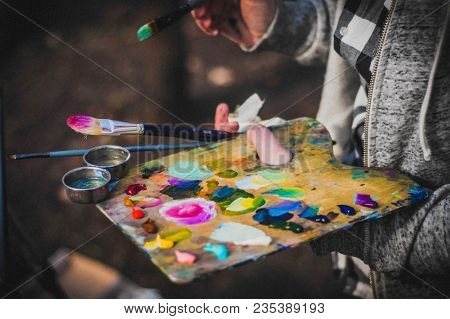 Palette And Paint Brush In Artist Hands. Artist Paints Oil Picture With Paint Brush In Hand Palette