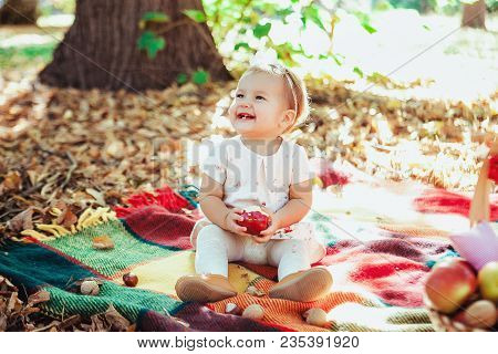 Cute Baby Girl Eating Apple Under Huge Tree On Green Grass At Sunny Beautiful Forest Background.