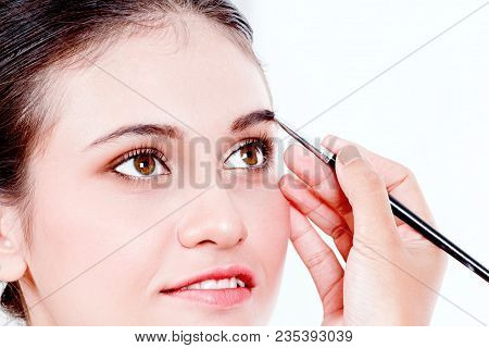 Stylist Applying Apply Makeup On A Eyebrows To The Beautiful Woman