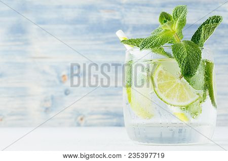 Fresh Cold Summer Beverage With Lime, Leaf Mint, Straw, Ice Cubes On Light Blue Wooden Background, C