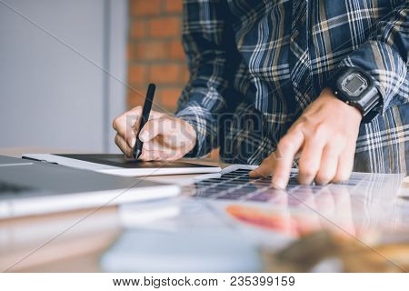Freelance Creative Designers Working On Desk Using Digital Graphic Tablet And Drawing With Pen In Mo