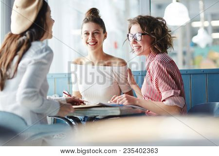 Adolescent groupmates in casualwear spending break between classes in college cafe and having talk