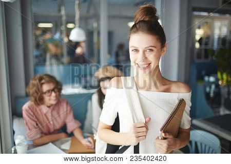 Smiling adolescent student with notepad and backpack going for next lesson while her friends preparing report for seminar on background