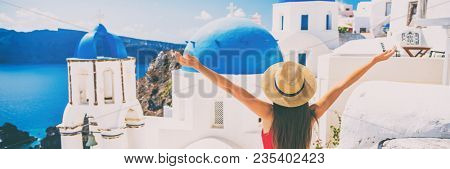 Happy girl tourist having fun in Santorini Europe travel vacation. Woman with arms out in happiness, banner panorama.