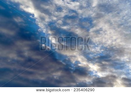 Dark Cumulus And Light Feathery Clouds On The Blue Sky. Cumulus Clouds Are On The Diagonal. From Lef