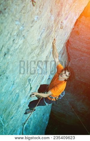 Man Rock Climber. Rock Climber Climbs On A Rocky Wall. Outdoor Climbing