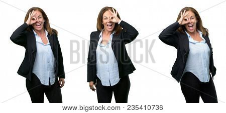 Middle age business woman looking at camera through her fingers in ok gesture. Imitating binoculars, beautiful eyes and smile over white background