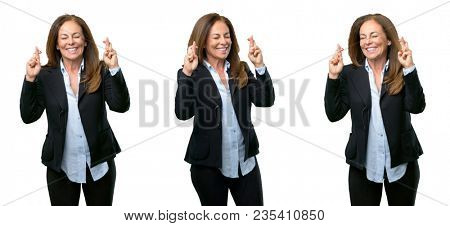 Middle age business woman with crossed fingers asking for good luck over white background