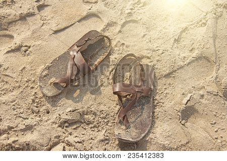 Brown Leather Flip Flops On The Sand. Couple.