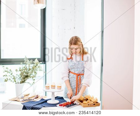 Young Pretty Blonde Woman Taking Strawberry And Decorating Tasty Cupcakes