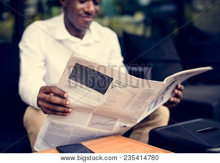 African descent man sitting reading a newspaper outdoor