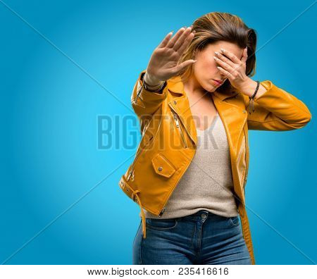 Beautiful young woman stressful and shy keeping hand on head, tired and frustrated, blue background