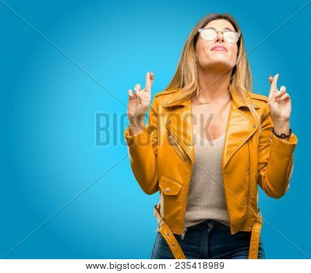 Beautiful young woman with crossed fingers asking for good luck, blue background