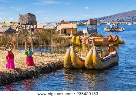 Puno, Peru - May 14, 2015: Unidentified Women In Traditional Dresses Welcome Tourists In Uros Island