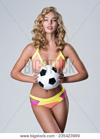Beautiful sexy woman in trendy swimsuit holds a soccer ball. Attractive young girl with classic soccer ball posing at studio
