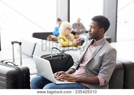 African-american businessman with laptop browsing in the net while waiting for flight announcement in airport lounge