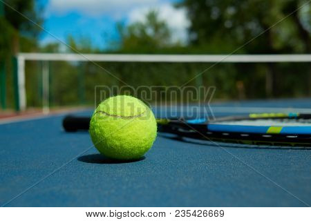 Close Up Of Yellow Ball Is On Tennis Racket Background, Laying On Blue Tennis Court Carpet. Photo Of