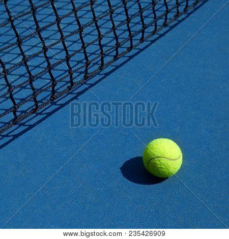 Yellow Bright Tennis Ball Is Laying Near Black Net.