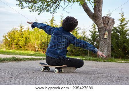 Kid Skateboarder Sitting On His Skateboard And Feels Happy.