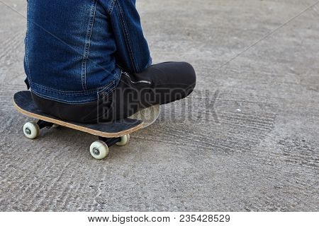 Kid Skateboarder Sitting On His Skateboard On The Ground.
