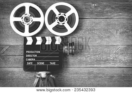 Old Movie Camera, Consisting Of A Tripod, Lens, Film Reels And Clapperboards.tblack And White Photo.