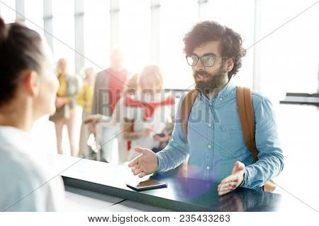 Indignant young man explaining something to manager at check-in counter during registration process