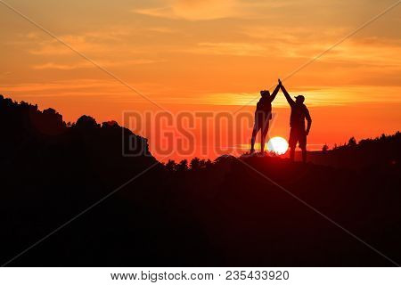 Teamwork Couple Celebrating Silhouette In Inspiring Mountains Sunset. Team Of Climbers Celebrate Rea