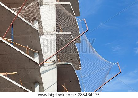 Unfinished Cement Building At A Construction Site. Brick Masonry Of The Balcony.