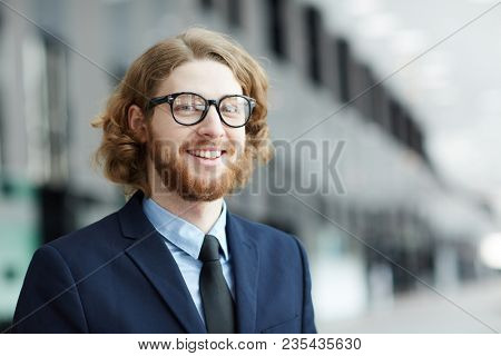 Young smiling bearded businessman in formalwear looking at camera inside modern building