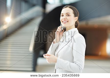 Young business leader in formalwear phoning her co-workers to gather them for meeting after travel