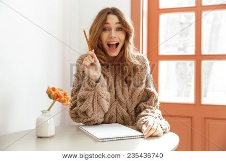 Portrait of excited woman in sweater with long brown hair sitting at table in coffee shop and writing down notes on paper
