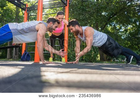 Two fit young men clapping hands from face to face plank position during partner workout motivated by their friend outdoors in the park