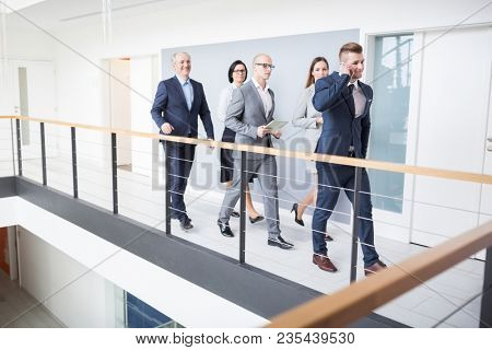 Full length of confident business team walking on corridor by railing in office