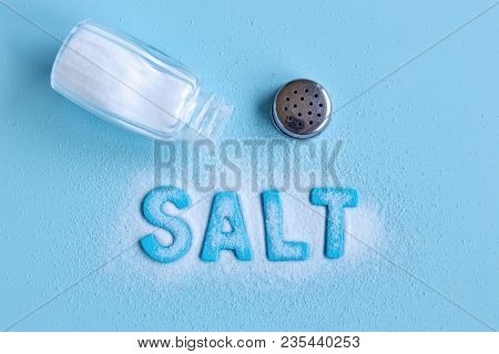 Blue letters spelling the word 'salt' and salt shaker on blue background
