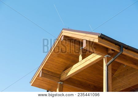 Lightning conductor on a wooden house. Blue sky. Security. Building. Technologies poster
