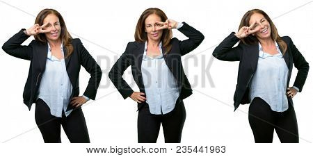 Middle age business woman looking at camera through her fingers over white background