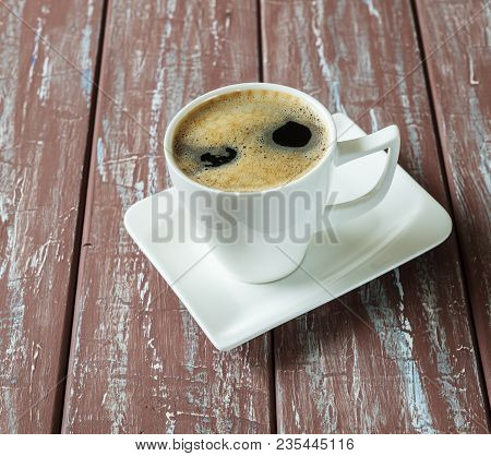 Hot Coffee In A White Coffee Cup With Saucer And Coffee Spoon On The Old Wooden Table