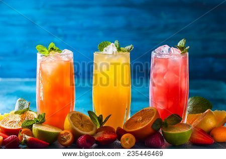Different types of summer drinks in glasses, cubes of ice and slice of fruits  on blue table. Healthy vitamin fruit and berry drinks.