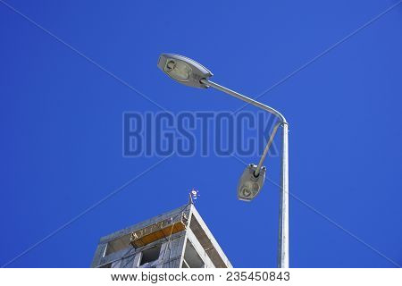 Unfinished New Building Isolated With Lantern Against A Blue Sky Background