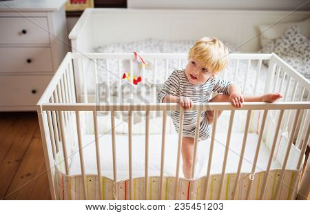 A Little Toddler Boy Getting Out Of A Cot. Domestic Accident. Dangerous Situation At Home.