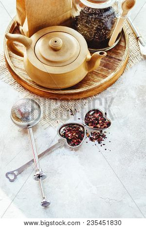 Ceramic Tea Pot, Metal Tea Infuser And Cup Of Black Tea. Composition With Tea Accessories On A White