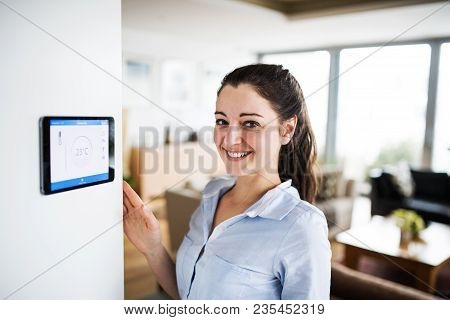 A Woman Looking At Tablet With Smart Home Control System.