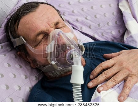 The old man in the hospital. CIPAP therapy or oxygen mask on her face