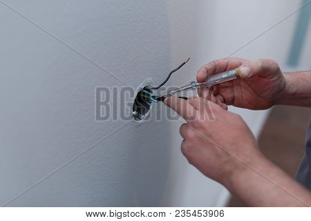 Close-up Of Hands Of An Electrician Installing New Electrical Switches During The House Renovation