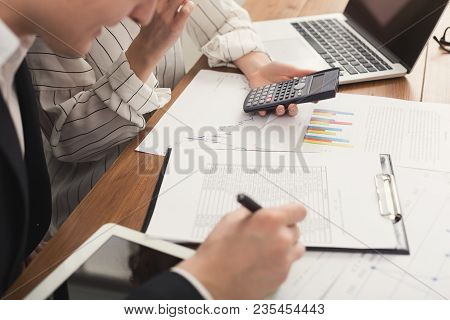 Closeup Of Business Partners Hands Working With Financial Documents And Counting On Calculator. Fina