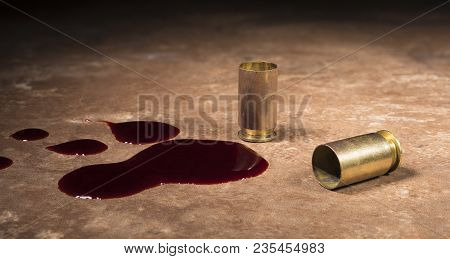 Blood Next To A Pair Of Empty Hulls From A Semi Auto Handgun On A Beige Floor